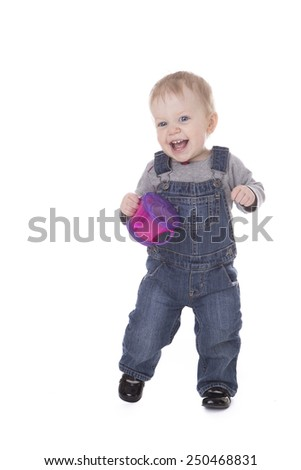 Baby girl in overalls holding purple cup and walking isolated on white - stock photo