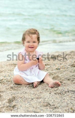Baby girl in pink and white dress sitting in the sand on the beach and smiling. Summer holiday.