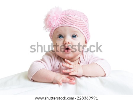 baby girl in pink knitted hat lying on white bed - stock photo