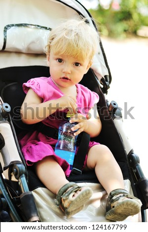 baby girl in pram with bottle of water