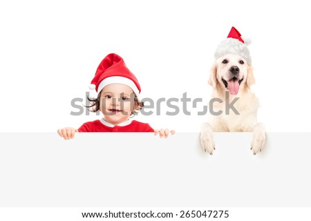 Baby girl in Santa Claus costume and a dog with Santa Claus hat posing behind a blank white billboard isolated on white background - stock photo