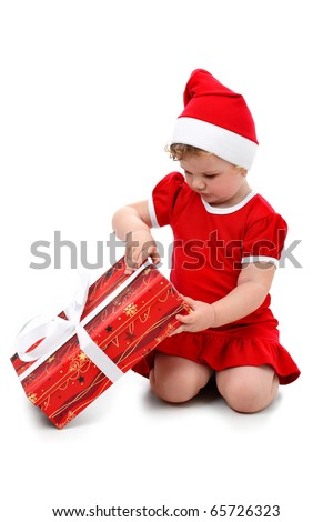 Baby girl in Santa's hat unpacking her Christmas present isolated on white - stock photo