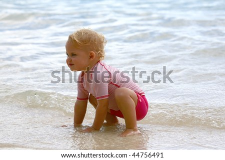 baby girl in shallow water at the beach