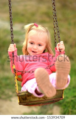 Baby girl in swing - stock photo