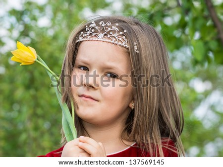 baby girl in the garden with a yellow flower - stock photo