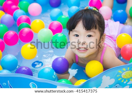 Baby girl in the inflatable pool with colorful plastic ball