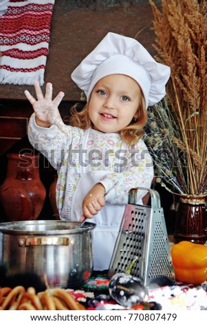 Baby girl in the kitchen cooking as a little chief