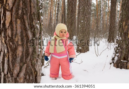 Baby girl in the winter forest - stock photo