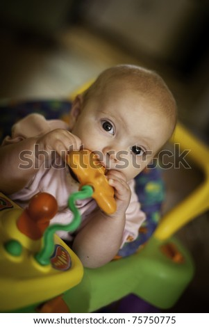 Baby girl in walker chewing on toy - stock photo