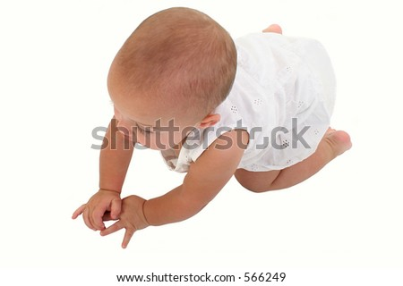 Baby girl in white crawling on floor.