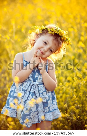 Baby girl in wreath in field - stock photo