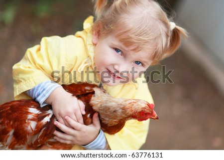 Baby girl in yellow holding hen - stock photo