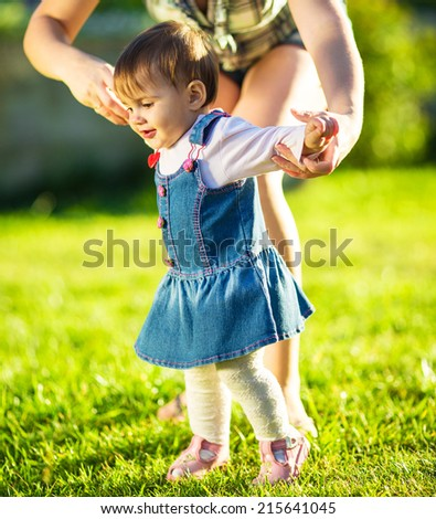Baby girl is doing her first steps with mothers help. Cute little girl learns to walk with her young mom helping her in the sunny garden outdoors. Happy childhood and motherhood concept.  - stock photo