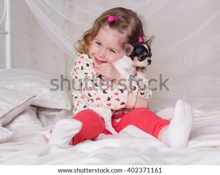 Baby girl is sitting on bed and hugging dog - stock photo