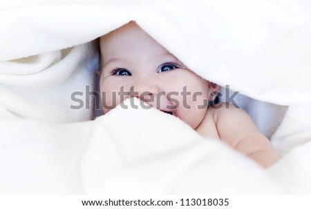 baby girl is wrapped in white blanket - stock photo