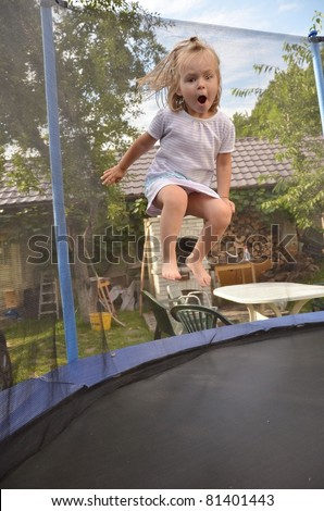 baby girl jumping on  trampoline - stock photo