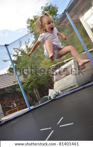 baby girl jumping on  trampoline
