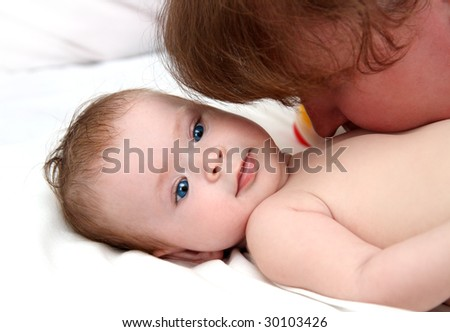 baby girl kissing by mother