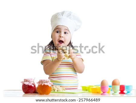 baby girl kneading dough in kitchen isolated - stock photo