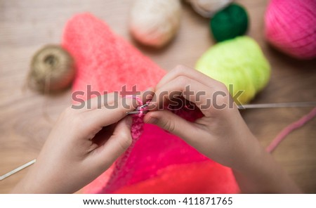 baby girl knitting pink scarf close up on a wooden table.