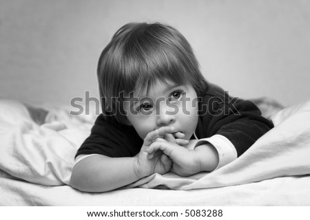 Baby girl laying on a sofa watching TV with ultimate attention - stock photo