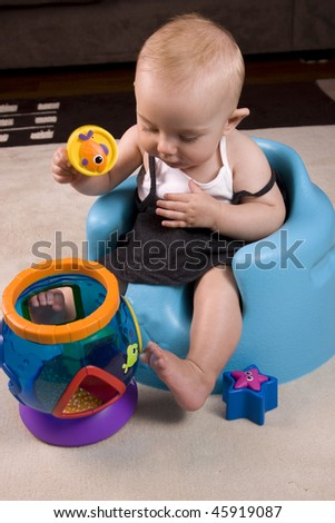 Baby girl learning new shapes - stock photo