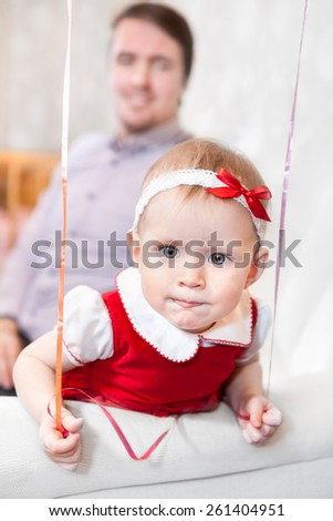 Baby girl looking at camera with father on background - stock photo