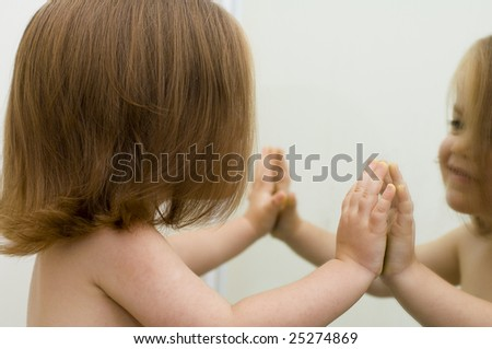 Baby girl looking at her reflection in the mirror and smiling - stock photo