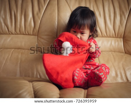 Baby girl looking for her gift in santa's sock on sofa