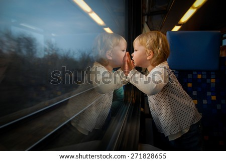 Baby girl looking through window. She travels on a train. - stock photo