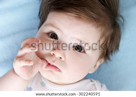 Baby girl looking up sucking on a finger
