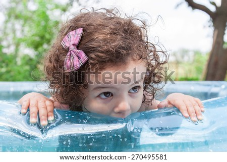 Baby girl looking with his hands on the edge of the inflatable pool - stock photo
