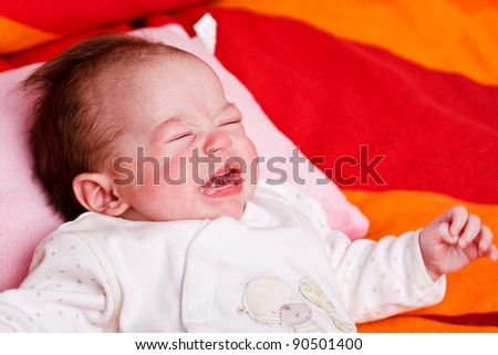Baby girl lying on a soft blanket and crying - stock photo