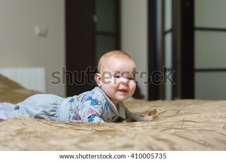 Baby girl lying on belly and grimacing - stock photo
