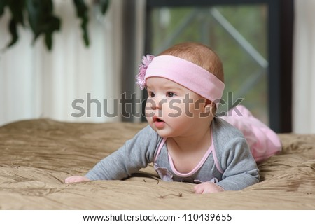 Baby girl lying on belly on bed in bedroom with golden linens. Charming 5-month-old girl smiling and grimacing. Home interior in background. - stock photo