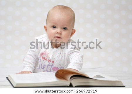 Baby girl lying on the belly reading a book and looking at the camera - stock photo