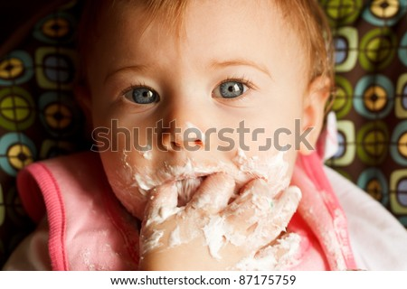 Baby girl making a mess while feeding herself cake - stock photo