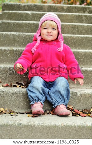 baby girl making funny face and sitting on the stairs - stock photo