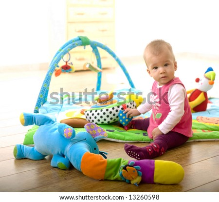 Baby Girl (9 months old) sitting on floor and playing with toys at home in living room. Toys are property released. - stock photo