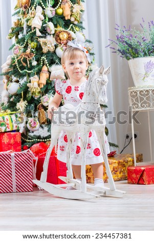 baby girl next to a horse rocking near a Christmas tree