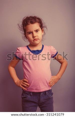 baby girl of European appearance 6 years hands on his hips, anger, unhappy on a gray background retro