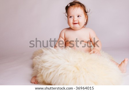Baby girl on a fluffy blanket - stock photo