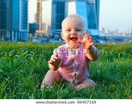Baby girl on a green grass on a modern city background