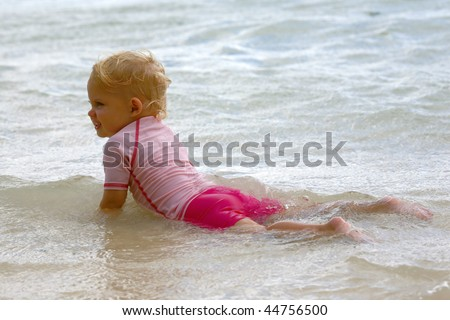 baby girl on her hands in water at the beach