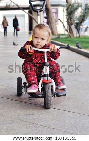 baby girl on her  tricycle on the walk - stock photo