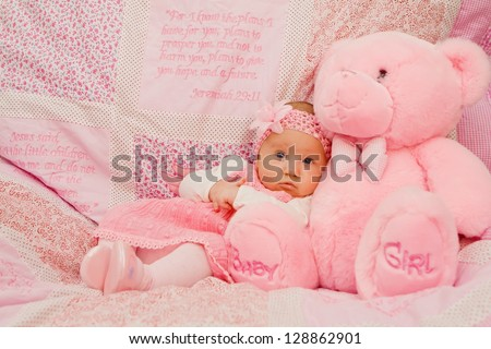 Baby girl on pink blanket with Bible verses - stock photo