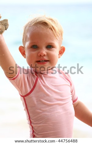baby girl on the beach showing sand in her hand