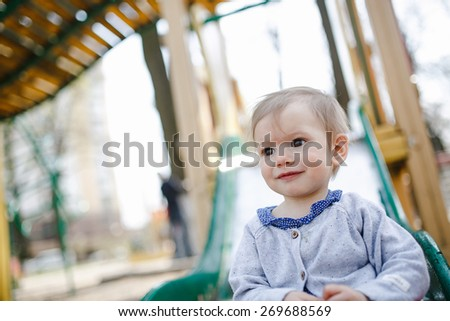 baby girl on the slide on the playground in spring - stock photo