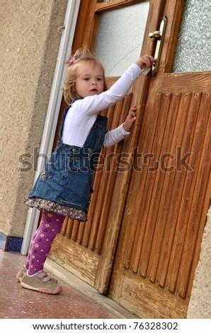 baby girl open the door - stock photo