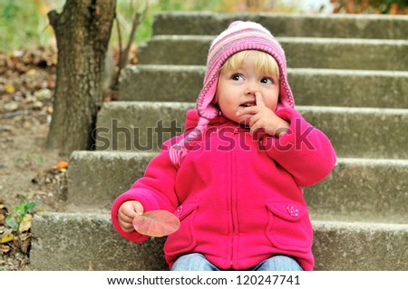 baby girl picking her nose outdoors - stock photo
